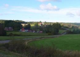 Gårdslägen i Skrammestad och Rishög på Bullaresjöarnas västra sida, typiska för områdets äldre bebyggelse. Gårdarna ligger i höjdlägen och omges av ett böljande jordbrukslandskap.