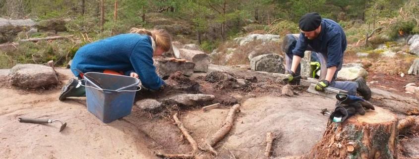 Annika och Benjamin rensar fram gravgömman under röset Tanum 1910, beläget vid Ljungbytorp,  som vi undersökte våren 2012.